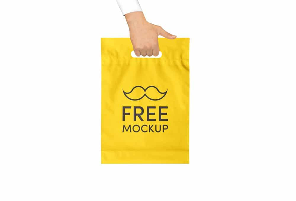 Hand holding Yellow Plastic Bag Free Mockup