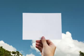 Free Hand Holding Paper Plus Sky Mockup in PSD